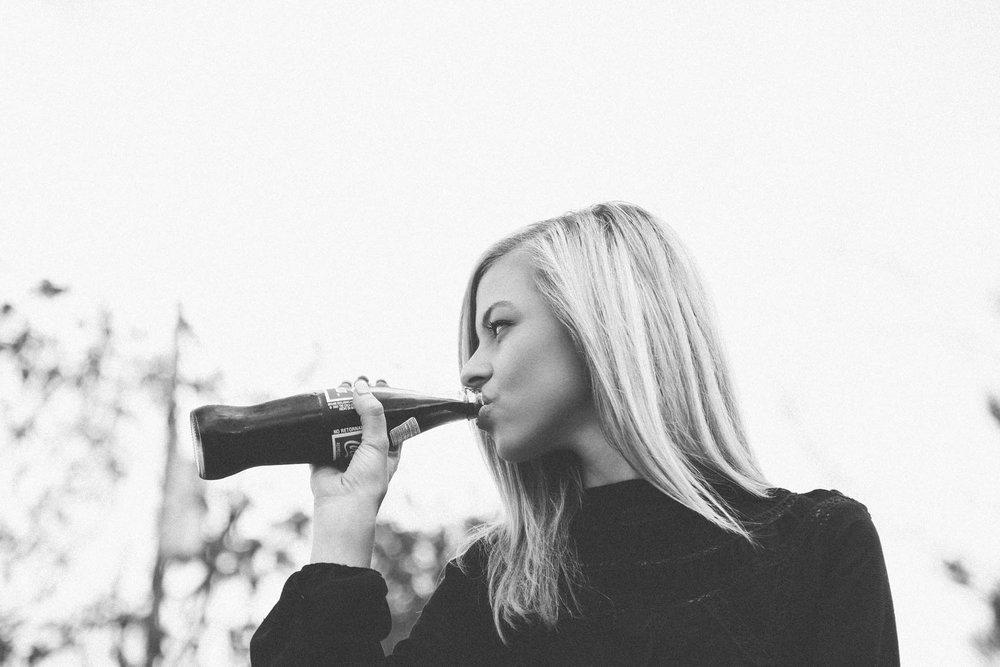 Esta mujer bebe un refresco porque tiene sed.