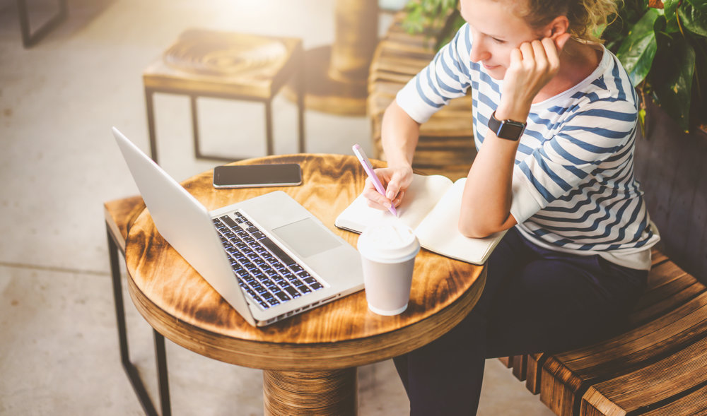 View from above.Young woman in striped t-shirt sitting at round wooden table in cafe and writing in notebook.In front of her is laptop,smartphone and cup of coffee. Online learning, freelancer.