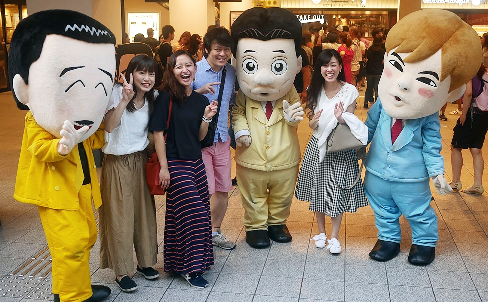 Yoshimoto fans get their picture taken with cartoonish representations of famous comedians.
