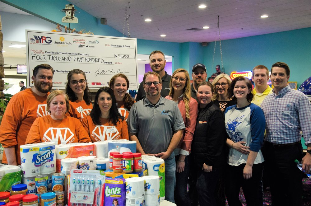 The ABC YPG Steering Committee presents a check for $4,500 and over $500 worth of pantry donations to Families in Transition-New Horizons