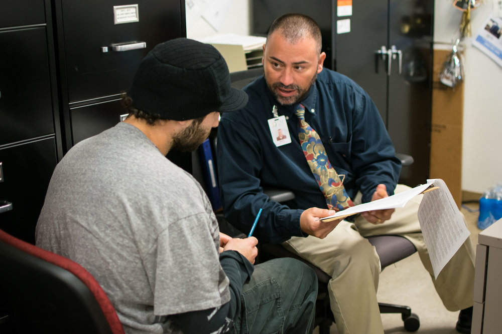 CSET Senior Program Specialist Miguel Castaneda assists a resident with their tax return during the 2016 tax season..jpg