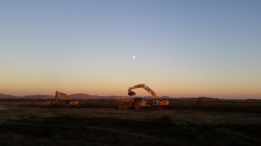 Loading Haul Trucks for Construction of Seperation Levee at Sunset