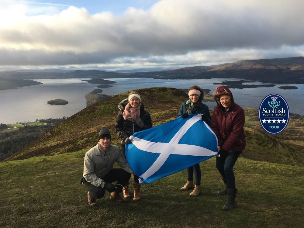 family posing at loch lomond with scotland flag