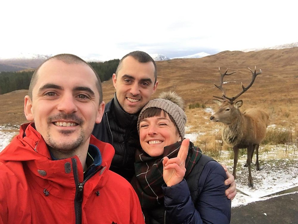 john with clients and a red deer stag in the highlands.jpg
