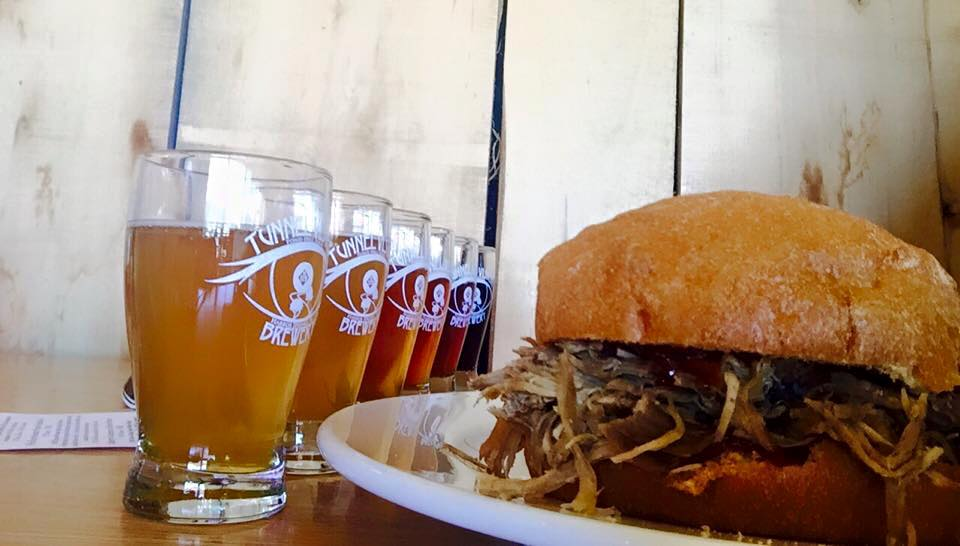 A flight of beer & a Pulled Pork Sandwich topped with our Cherry Wine BBQ Sauce