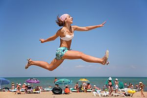 The woman jumps on a beach.