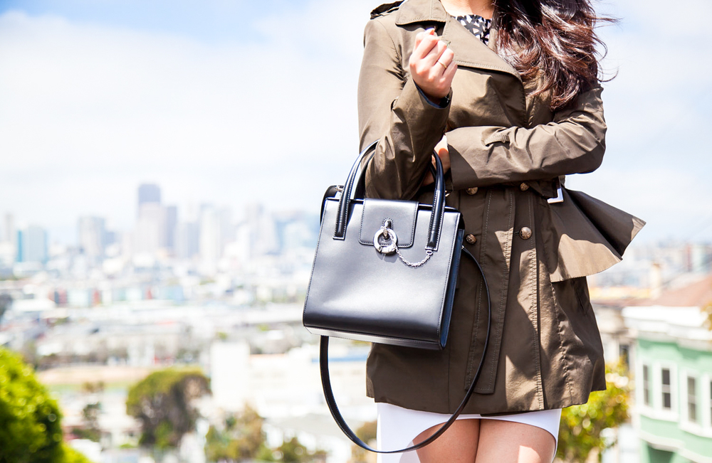 Peplum olive trench coat and structured Cartier bag