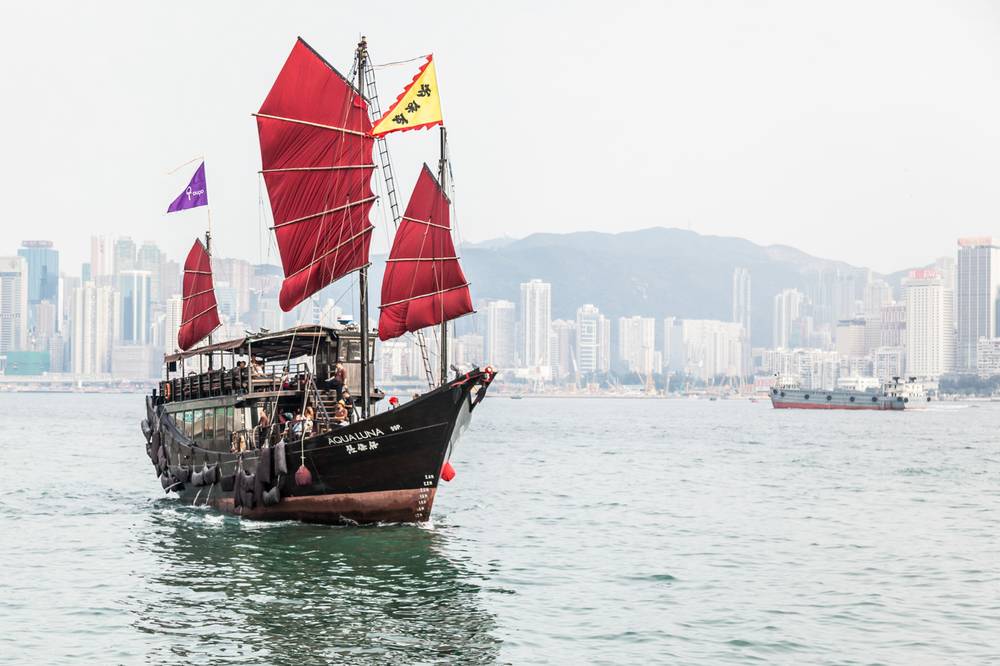 Aqua Luna - a red sail Chinese junk boat sailing through Hong Kong's Victoria Harbour.