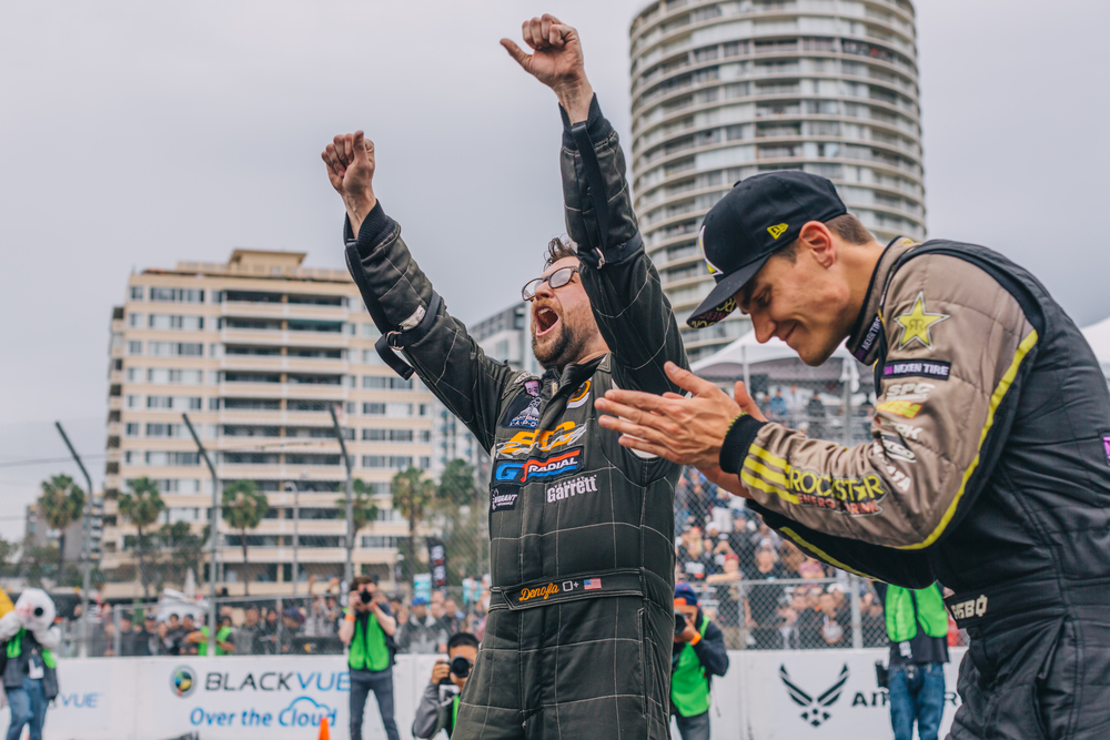 Chelsea Denofa celebrates beside runner-up Fredrick Aasboø as Denofa's name gets announced as the 2016 Formula Drift Long Beach Champion.