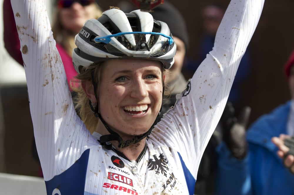 Ellen Noble lifts her bike in victory after crossing the line for her second U23 Cyclocross National Championship.