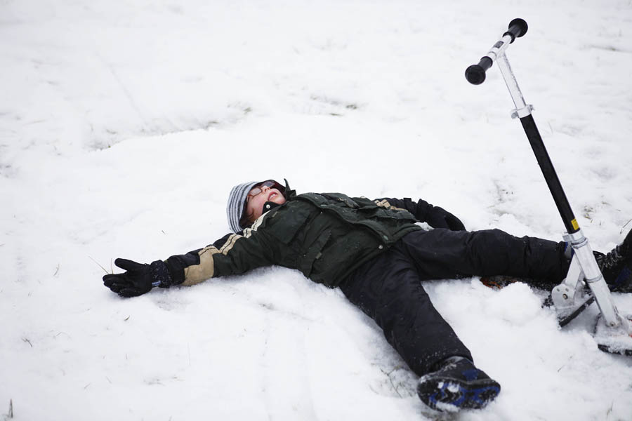 boy laying in the snow