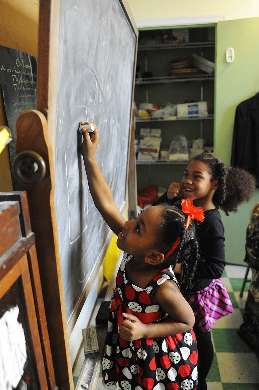 Englaind Ware, 5, and cousin Eliyrah Ware, 6, play school on a chalkboard during a soul food lunch at Ebenezer Baptist Church on Sunday, Feb. 24, 2013, in Staunton. The soul food spread included cornbread, baked beans, macaroni and cheese, fried chicken, corn, chitlins and pigs feet, plus an array of desserts.