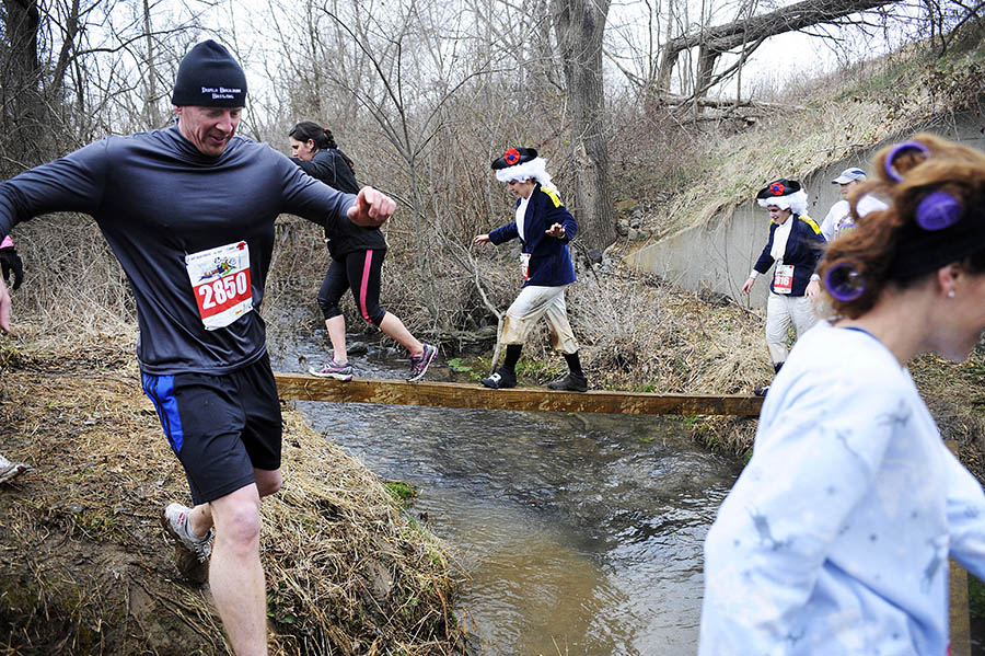 "Participants make their way across a creek over balance beams before braving a dark tunnel during the ""Mad Anthony"" mud run on Saturday, Feb. 23, 2013, at Coyner Springs Park. Almost 200 runners braved the 4-mile trek where they had to hop through a tire pit, climb walls, make their way through the muddy woods, and scale multiple hay bales."