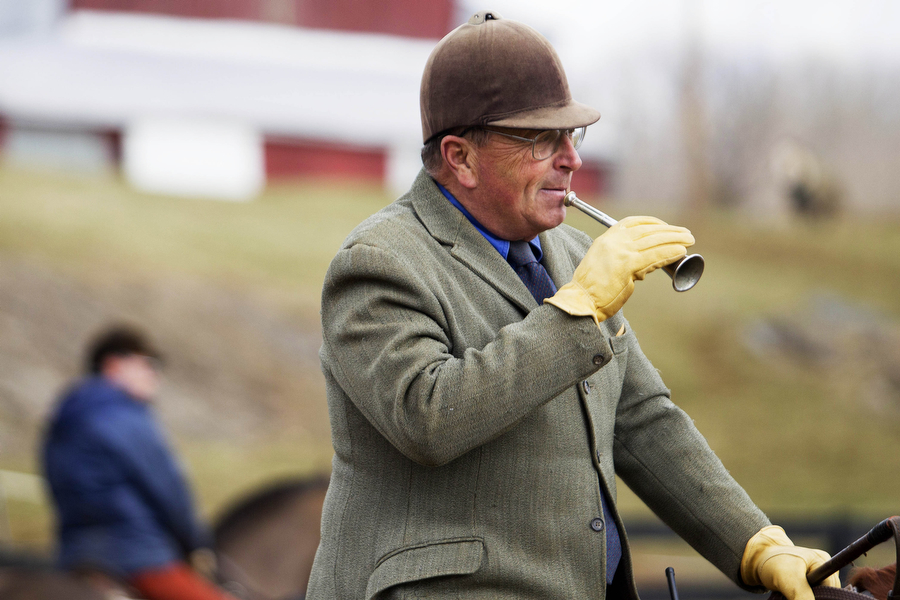 Huntsman Fred Getty blows his horn to call the hounds before setting off on the hunt on Wednesday, March 13, 2013 in Middlebrook. Getty has different calls on the horn that signal various things to both the hounds and the rest of the riders.