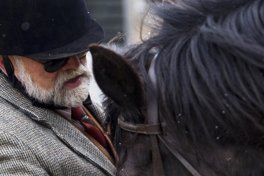 "Joe Patteson adjusts the bridle on his horse, Schuster, on Wednesday, March 13, 2013, in Middlebrook. Contrary to the name, foxhunts rarely result in the killing of a fox. Many riders say it is more of a ""fox chase,"" and admire the cleverness of the fox."