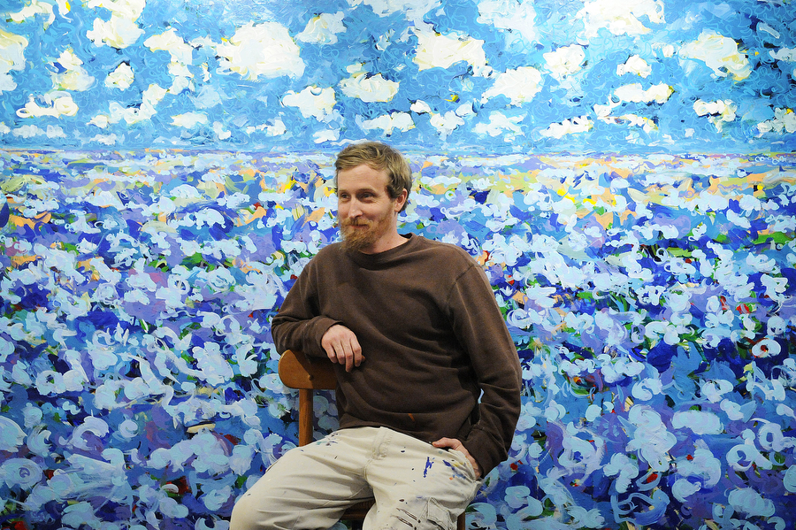 "Del Hall sits in front of an unfinished painting in his studio off of the Blue Ridge Parkway. Hall is part of a new art movement of young artists called SatRealism. ""When you're doing whatever it is you're doing with an open heart, you can hear those whisperings inside you,"" he said. ""Everyone has that voice. For me, I feel that I can hear the divine."""