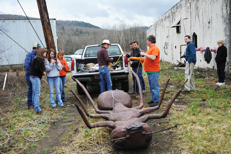 The group ties a cable around the base of a large ant sculpture to pull up on top of a water tower at the abandoned Stillwater plant on Sunday, March 31, 2013, in Goshen. The ant was a part of an April Fools prank by Mark Cline, who is notorious in the Shenandoah Valley for his annual elaborate sculpture-based pranks, such as Foam Henge.