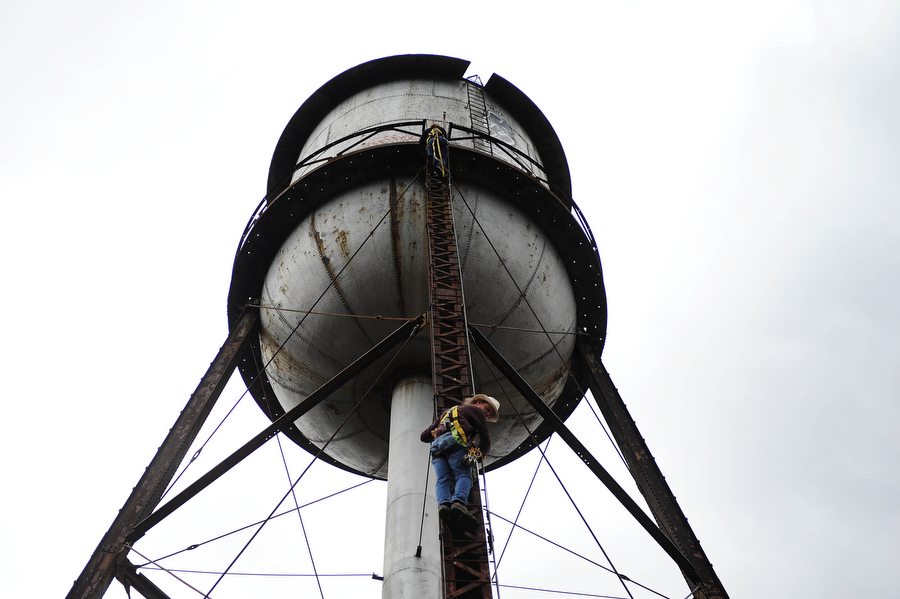 Mark Cline and Lee Harris climbs a water tower at the abandoned Stillwater plant on Sunday, March 31, 2013, in Goshen. Cline does an April Fools prank every year — this year, placing a large ant sculpture on top of the water tower in Goshen. Cline is notorious in the Shenandoah Valley for his annual elaborate sculpture-based pranks, such as Foam Henge.