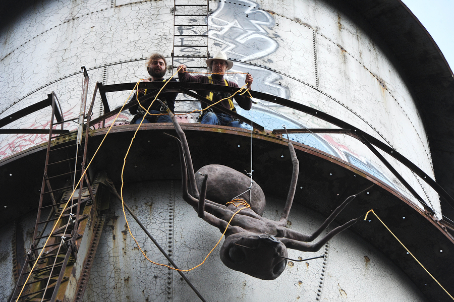 Mark Cline and Lee Harris pull a large ant sculpture up to the top of a water tower at the abandoned Stillwater plant on Sunday, March 31, 2013, in Goshen. Cline does an April Fools prank every year — this year, placing a large ant sculpture on top of the water tower in Goshen. Cline is notorious in the Shenandoah Valley for his annual elaborate sculpture-based pranks, such as Foam Henge.