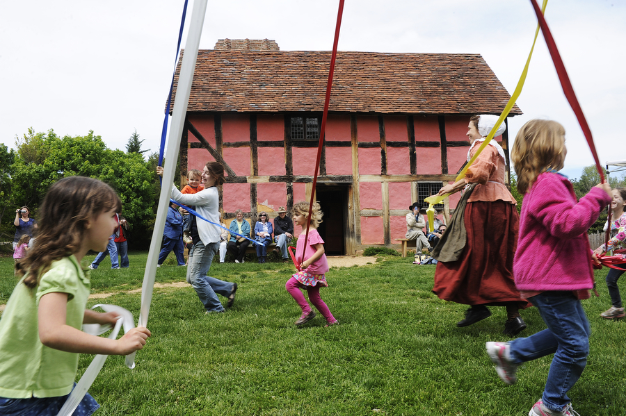 Children and adults dance around the May Pole during May Day festivities at the Frontier Culture Museum on Saturday, May 4, 2013, in Staunton. Participants learned a variety of patterns and weaves around the May Pole for the celebration of spring.