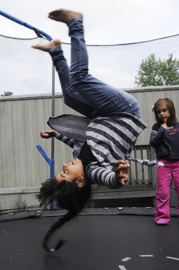 Magy Altamirano, 7 does a flip on the trampoline as Camila Suarez Nuñez, 5, watches, eating a lollipop, on Friday, May 3, 2013, in Staunton. The three had just gotten home from school and gotten off the bus.