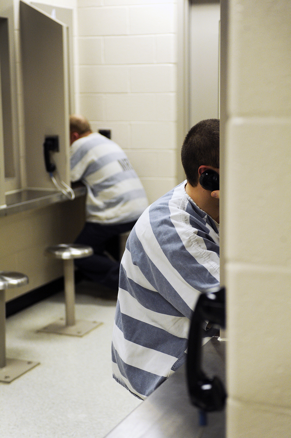 Inmates sit in cinderblock booths to talk to their visitors through plastic phones at Middle River Correctional Jail on Friday, May 3, 2013, in Staunton. The visitation room has 18 booths where visitors and inmates can talk through plastic phones.