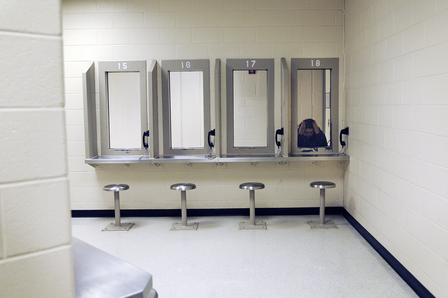 A visitor holds her head in her hands as she waits for the inmate she's visiting to enter the visitation room at Middle River Correctional Jail on Friday, May 3, 2013, in Staunton. The visitation room has 18 booths where visitors and inmates can talk through plastic phones.