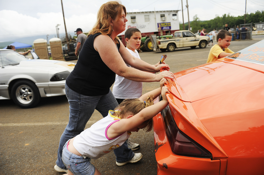 McKenzie Flusher, 5, of Keezletown pushes a family friend's car to the track with her mother and brother during a drag racing event at Eastside Speedway on Sunday, June 2, 2013, in Dooms. The drag races involved street cars, footbrake, super pro, motorcycles and dragsters.