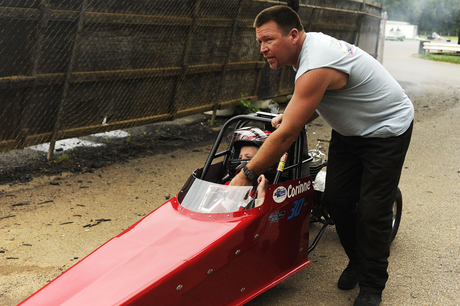 Chris Campbell pushes daughter Corinne, 8, to the track where she will compete in junior dragster time trials at the Eastside Speedway on Sunday, June 2, 2013, in Dooms. The drag races involved street cars, footbrake, super pro, motorcycles and dragsters.