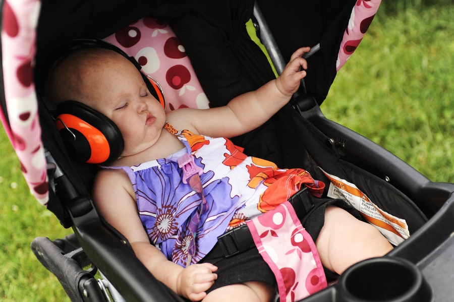 Josslynne Wildman sleeps soundly in her stroller during a drag racing event at Eastside Speedway on Sunday, June 2, 2013, in Dooms. The drag races involved street cars, footbrake, super pro, motorcycles and dragsters.