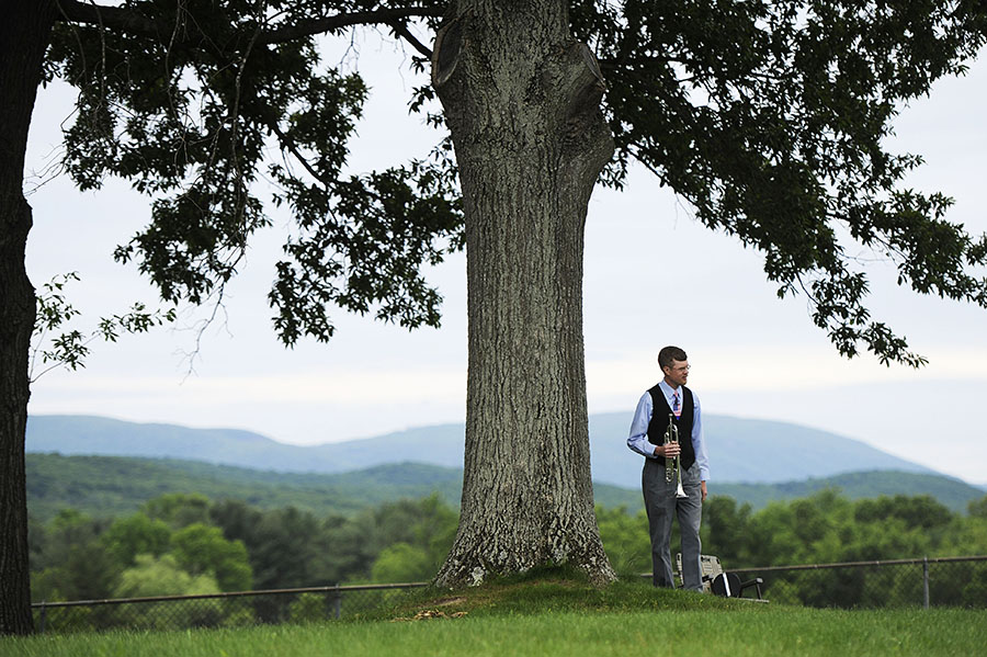 "John Fiske of Waynesboro stands by a tree as he waits to play ""Taps"" during a Memorial Day ceremony at Riverview Cemetery on Monday, May 27, 2013, in Waynesboro."