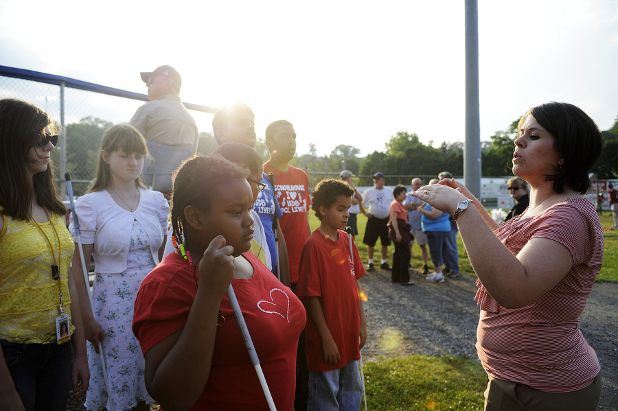 Music teacher Jessica Strawderman directs the choir from the Virginia School for the Deaf and Blind before the Staunton Braves game on Wednesday, June 5, 2013, in Staunton. Students from VSDB performed the National Anthem before the game, with some students signing and some students singing a cappella.
