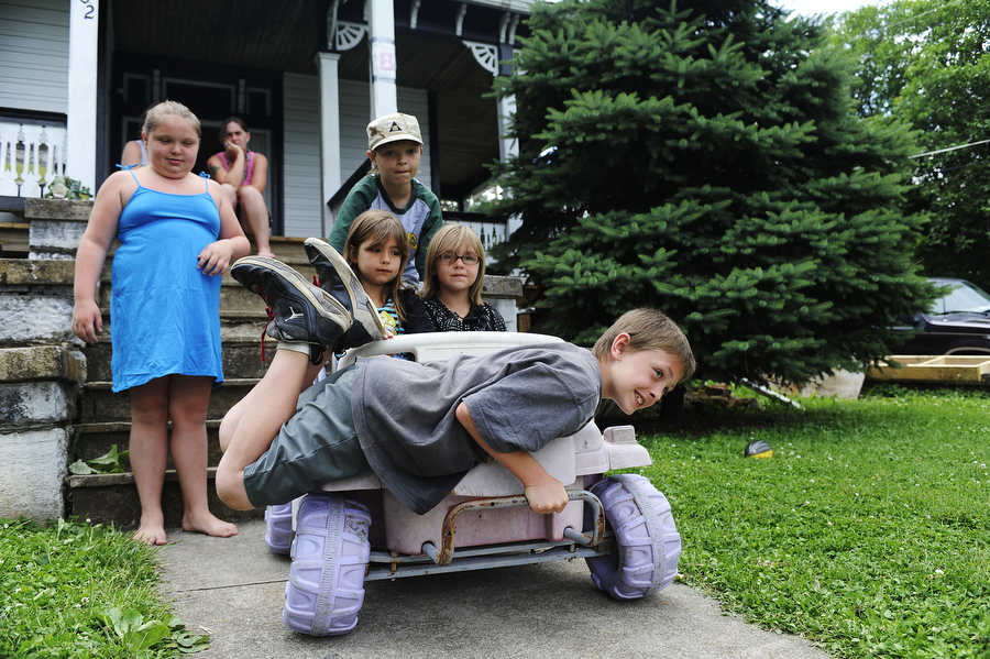 Zepplin Keller, 10, hangs on the front of a ride-on toy car as it rolls down the hill in his front yard Monday, June 24, 2013, in Staunton. Keller, his siblings and his neighbors took turns riding different things with wheels down the hill, from skateboards to even small toy dump trucks.