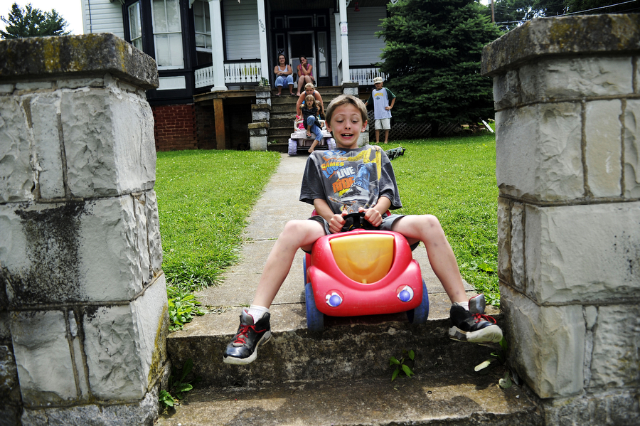 Zepplin Keller, 10, rides a plastic toy car down the hill and steps of his front yard as his siblings and neighbors watch Monday, June 24, 2013, in Staunton. The group of siblings and neighbors took turns riding different things with wheels down the hill, from skateboards to even small toy dump trucks.