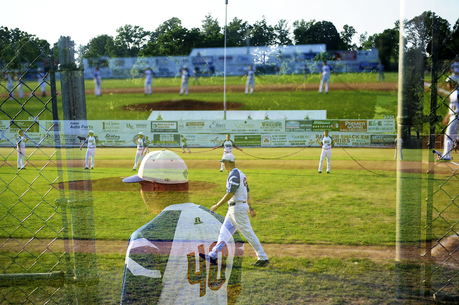 Double exposure frame showing Braves teammates prepping the field for the baseball game against Winchester over a frame of Braves' coach George Laase standing in the dugout on Tuesday, June 26, 2013, in Staunton.
