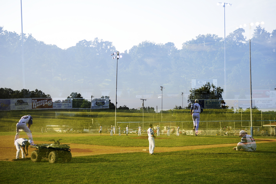 Double exposure frame with two pictures showing preparation of the field and players warming up before the baseball game against Winchester on Tuesday, June 26, 2013, in Staunton.
