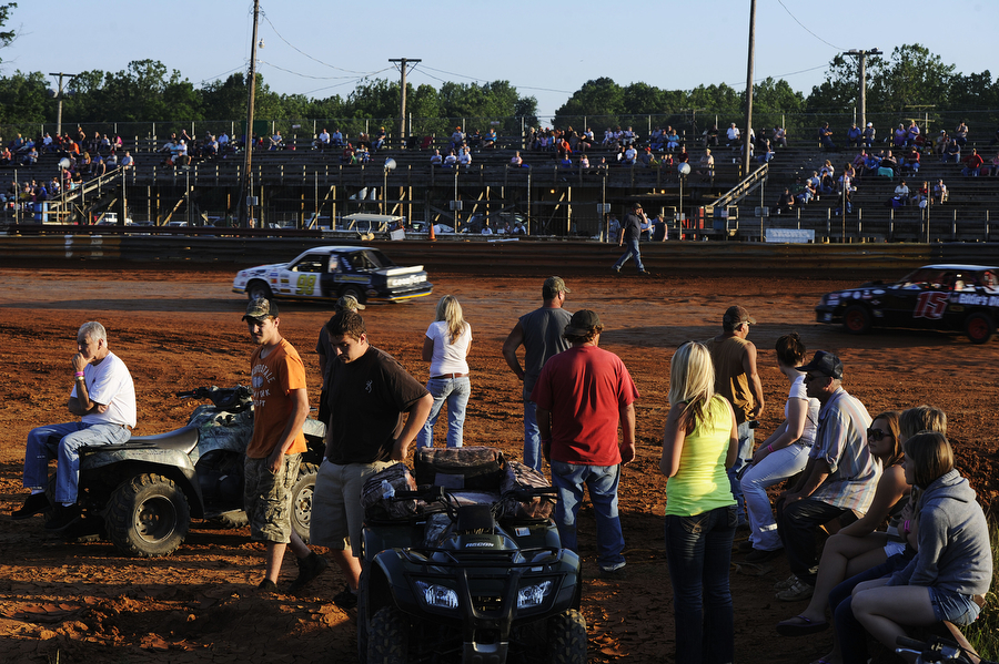 People who serve on pit crews gather in the middle of the track to watch the race during the dirt track races at Eastside Speedway on Friday, June 21, 2013, in Waynesboro.