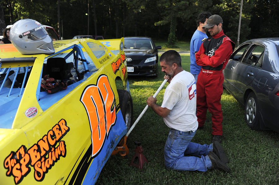Jeff Wimer lowers the jack as son and driver Jakob Wimer looks on before the dirt track races at Eastside Speedway on Friday, June 21, 2013, in Waynesboro.