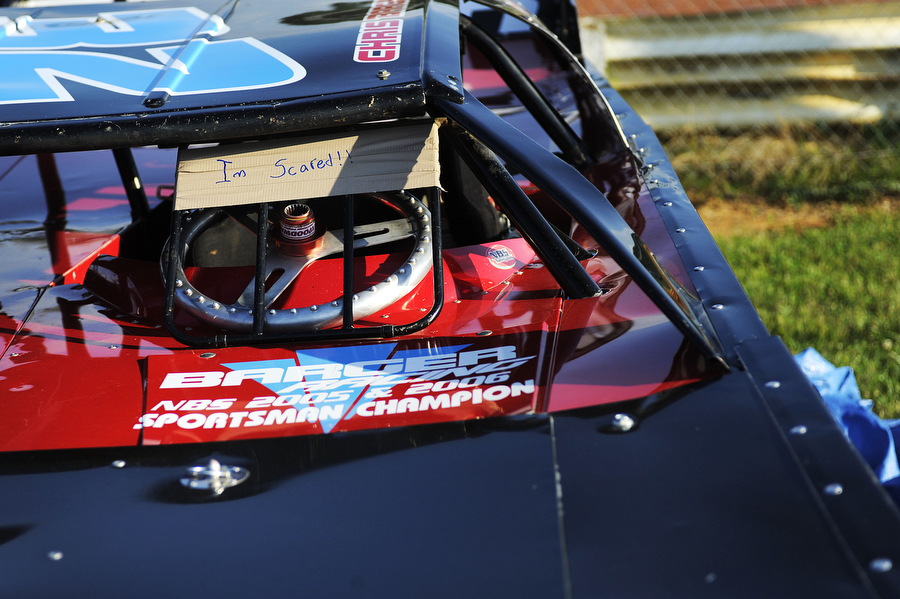 "Duct tape with the words ""I'm scared!"" cover the bars protecting the driver's seat on a racing car at Natural Bridge Speedway on Saturday, June 29, 2013, in Natural Bridge. Many cars no longer have windshields for racing anymore, due to the weight which can be used elsewhere, and bars and helmets instead protect the driver from mud and flying debris."