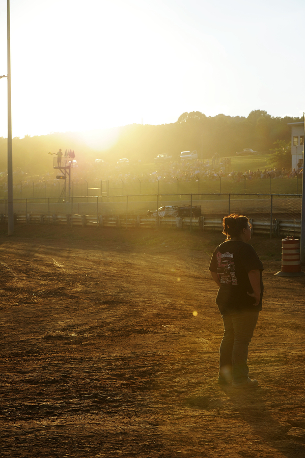 A woman watches the drivers from inside the track on Saturday, June 30, 2013, in Natural Bridge.