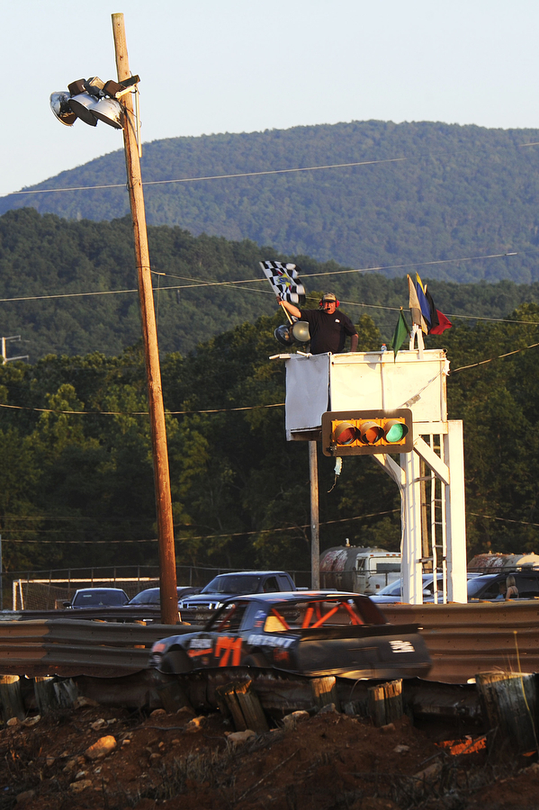 A man waves a flag signaling to the racers during the super stock division during the dirt track races at Eastside Speedway on Friday, June 21, 2013, in Waynesboro.
