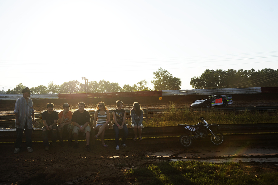 People who serve on pit crews gather in the middle of the track to watch the race as Petie Coffey drives by in the late model division during the dirt track races at Eastside Speedway on Friday, June 21, 2013, in Waynesboro.