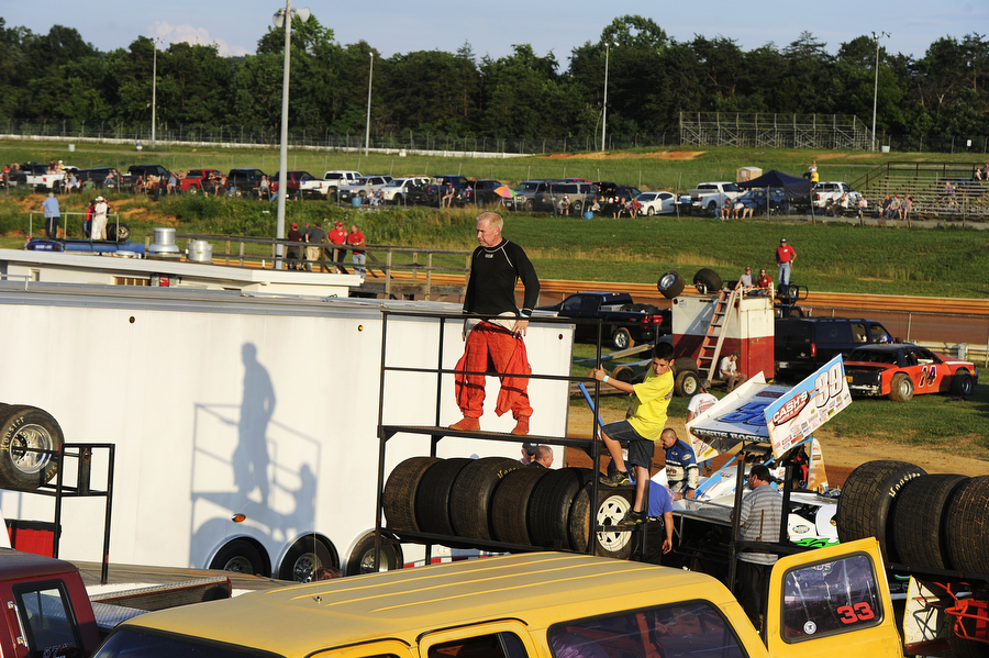 Drivers and pit crew watch the other races from inside the dirt track in the pit at Natural Bridge Speedway on Saturday, June 29, 2013, in Natural Bridge. At Natural Bridge, there is a metal fence that separates outsiders from entering the track. It's only opened when cars are off the course, though there have been occasions where spectators have crossed to visit Pit Road during warm-up laps.