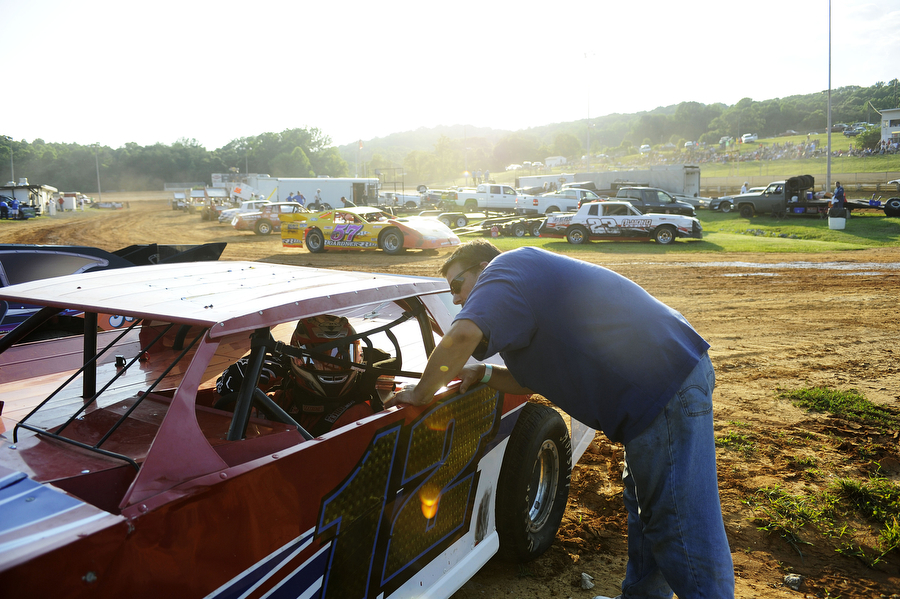 Ryan Adams, 22, talks to his father, Chris Adams, as his dad straps him into his car before he heads out to race in the sportsman division at Natural Bridge Speedway on Saturday, June 29, 2013, in Natural Bridge. Late model and sportsman series races often offer the biggest payout to the night's winner, sometimes going as high as $1,500.