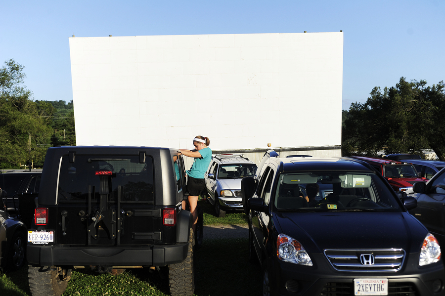 A girl hangs out the window of a Jeep at Hull's Drive-In Theatre on Saturday, July 6, 2013, in Lexington. The theater can fit around 300 cars, though manager Jeremy Reter says he often tries to squeeze in as many people as possible, and says 365 cars came on Friday, July 5. Sometimes, he has cars park behind the screen and lets people come in without their vehicles to still see the movie.
