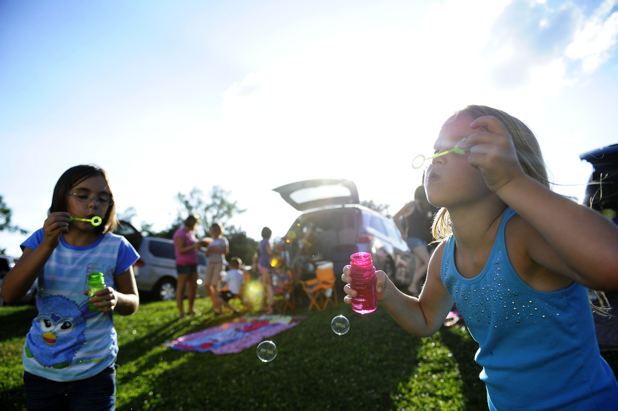 Cousins Alyza Kudro, 8, of Staunton and Aubrey Kudro, 7, of Waynesboro, blow bubbles while waiting for the movie to start at Hull's Drive-In Theatre on Saturday, July 6, 2013, in Lexington. The gates at the theater open at 6, but the show doesn't start until 9, so families often bring dinner, games and toys to keep their children entertained until it gets dark.a