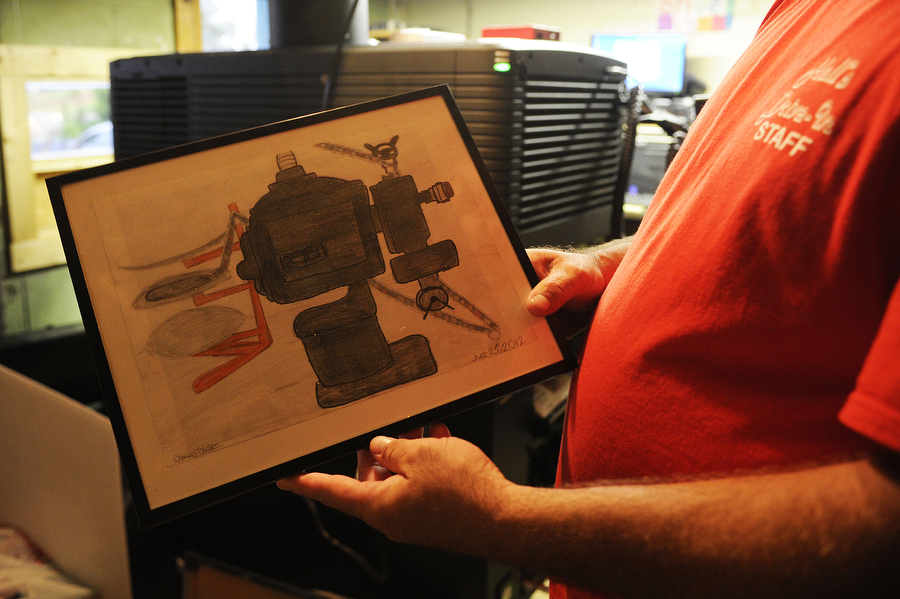 Manager Jeremy Reter holds up a picture of the old film projector drawn last year by his daughter, Charissa, in the projection booth at Hull's Drive-In in Lexington. The theater switched to a digital format last year, though they still have remnants of the film projector around, such as this picture and a few old reels.