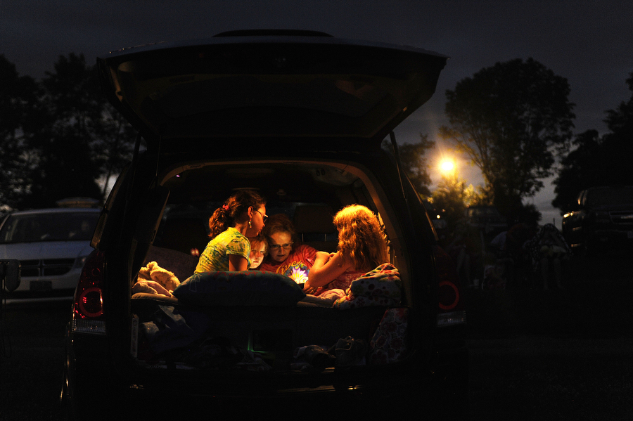 Theresa Evans, daughters Serena, 6, and Olivia, 10, and friend Sarah Dudley, 10, of Raphine play a game in the back of a van at Hull's Drive-In Theatre on Sunday, July 7, 2013, in Lexington.