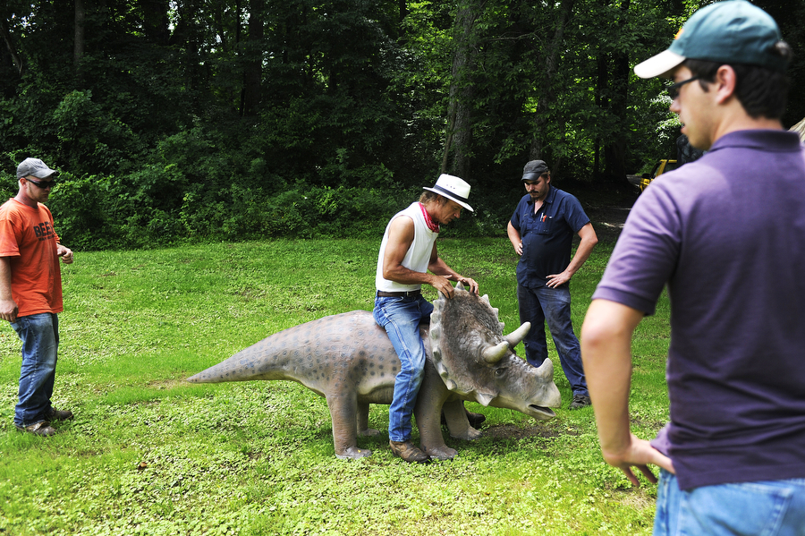 Mark Cline shows others how the triceratops he made was made for sitting on at Grand Caverns on Tuesday, July 9, 2013 in Grottoes. Cline brought four dinosaurs to the park in hopes of eventually expanding the project to increase tourism.