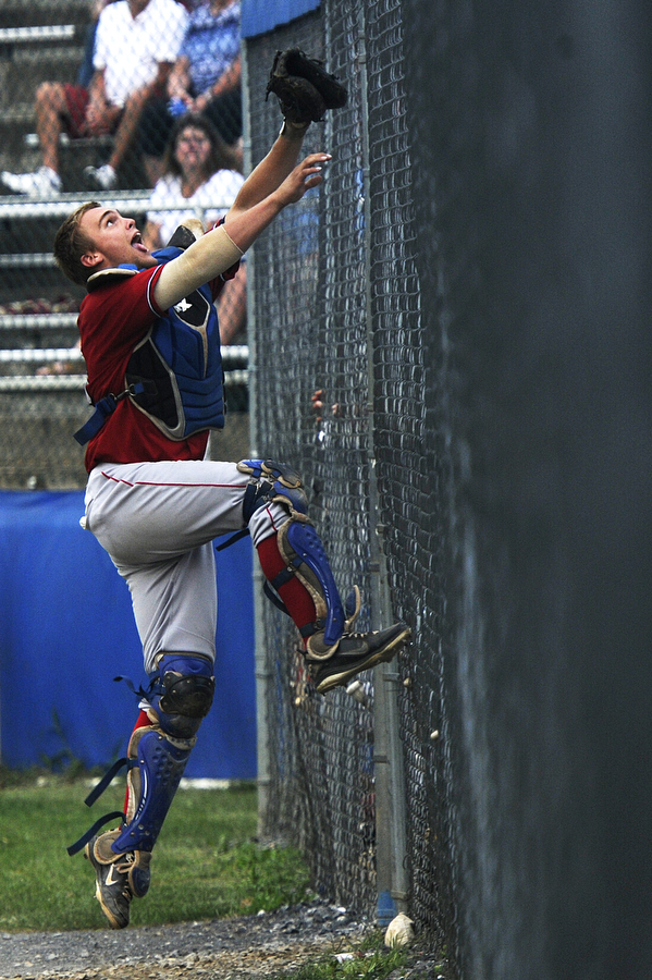 Turks' Joey Roach attempts to climb the chain link fence in front of the dugout to catch a foul ball during the baseball game against the Staunton Braves on Thursday, July 18, 2013, in Staunton.
